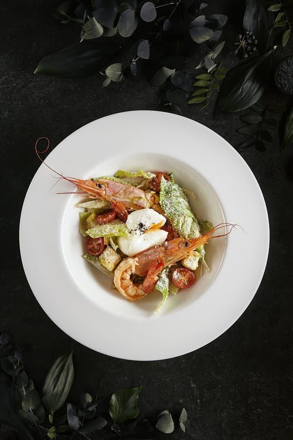 Placa blanca del restaurante de Caesar Salad con los camarones, pollo, cuscurrones, tomates, opinión superior de los pepinos fotos de archivo