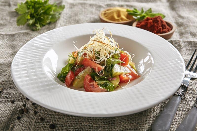 Placa blanca del restaurante de la ensalada vegetariana vegetal con las tiras de queso ahumado imagen de archivo
