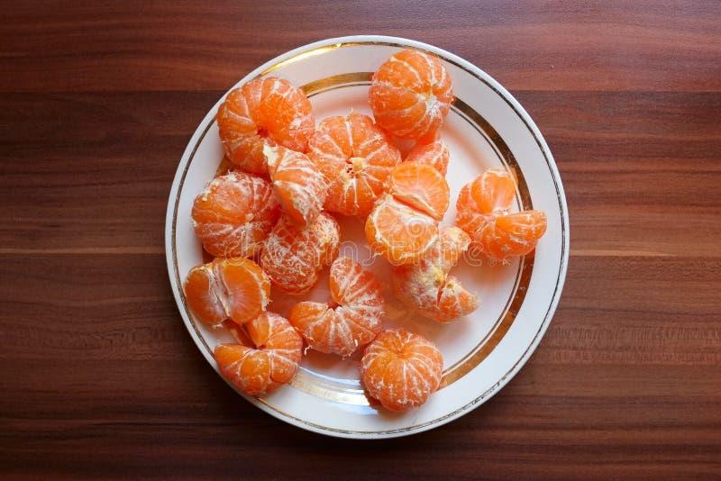 Placa blanca redondeada con la porci?n de fruta c?trica pelada anaranjada de la mandarina del mandar?n fotos de archivo libres de regalías
