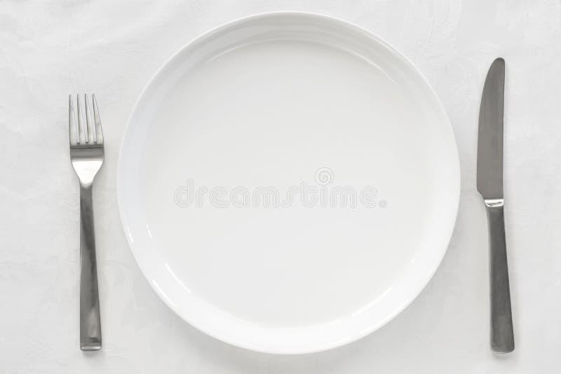 Placa blanca vacía en el brocado con la opinión superior del cuchillo y de la bifurcación foto de archivo