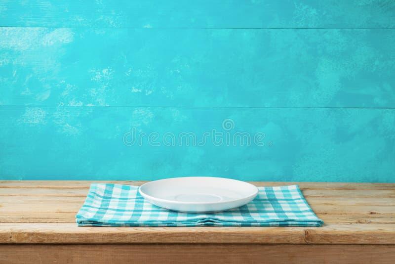 Placa blanca vacía en la tabla de madera con el mantel sobre la parte posterior azul foto de archivo