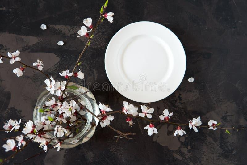 Placa blanca vacía y ramas de florecimiento en un florero en una opinión de top oscura del fondo imagen de archivo libre de regalías