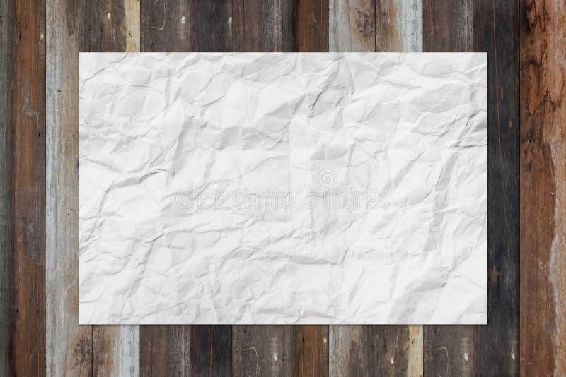 A placa branca amarrotou o papel na tabela de madeira do grunge imagem de stock royalty free