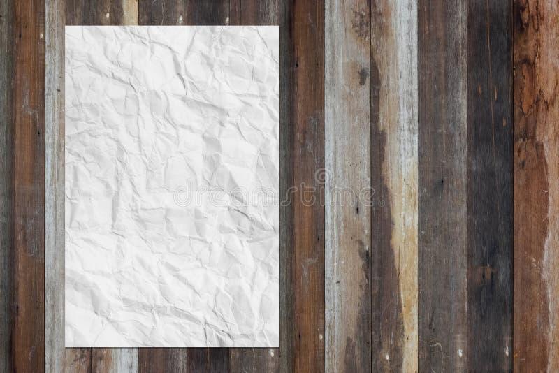 A placa branca amarrotou o papel na tabela de madeira do grunge foto de stock royalty free
