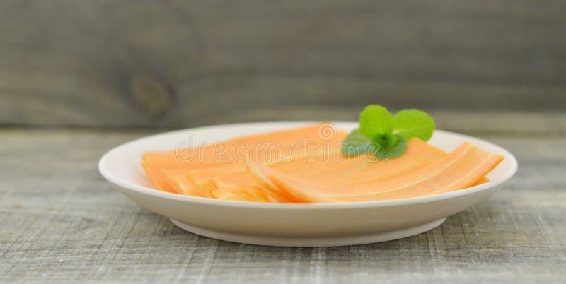 Placa branca com as cenouras e a hortelã das fatias finas na tabela de madeira imagens de stock
