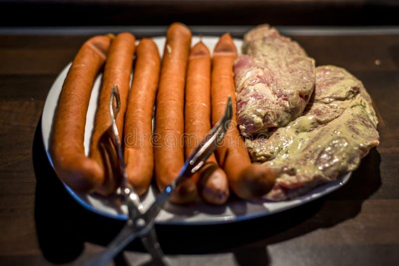 A placa branca com carne para grelhar salsichas do BBQ, cru ascendente próximo do bife apronta-se para o fogo imagens de stock royalty free