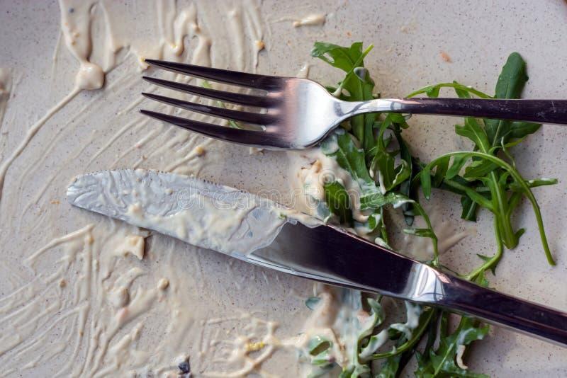 Placa branca com os restos do molho e dos verdes, em que se encontram uma faca e uma forquilha fotos de stock royalty free