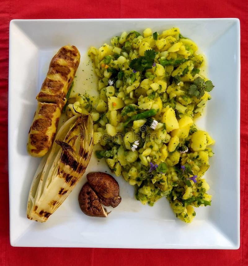 Placa branca com salada grelhada do alimento e de batata em um backgrou vermelho fotografia de stock