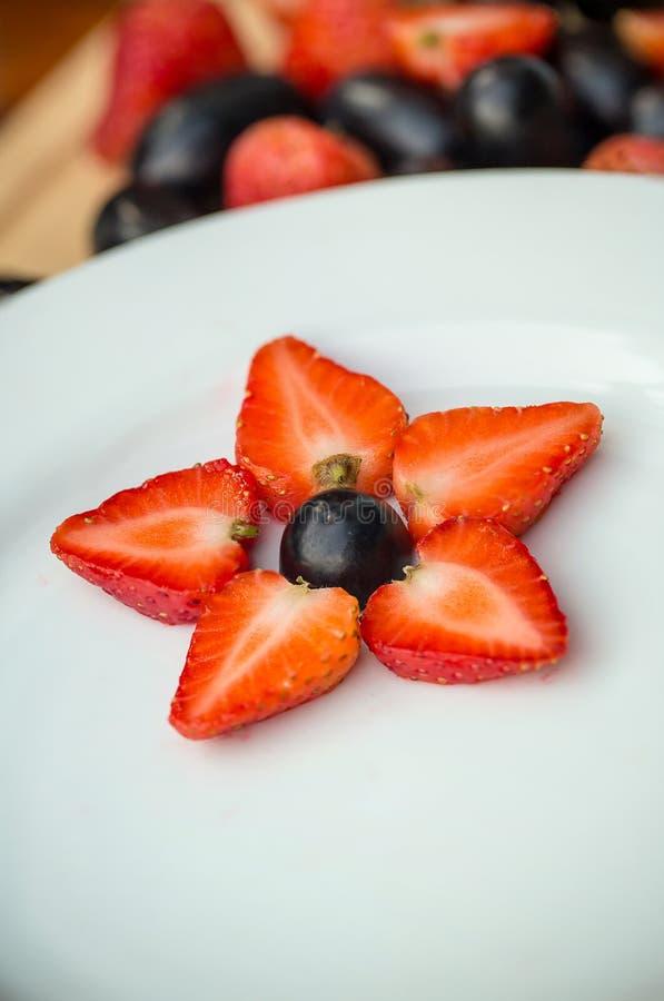 Placa branca com uvas e morangos, formulário da estrela imagens de stock
