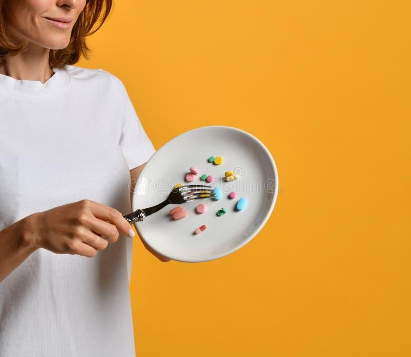 Placa branca da posse da m?o do nutricionista da mulher com as drogas diferentes da perda de peso da prescri??o dos suplementos d imagens de stock royalty free