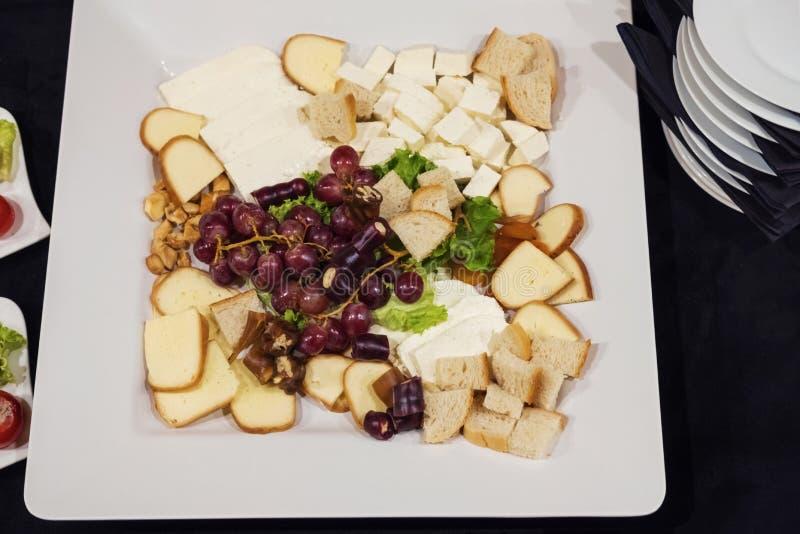 Placa branca das fatias misturadas do queijo imagem de stock royalty free