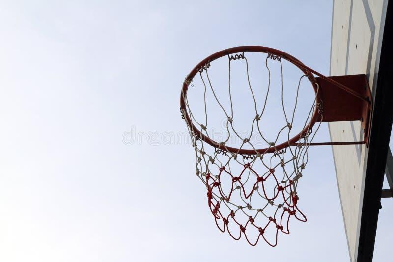 Placa branca do basquetebol com aro vermelha e da malha branco-vermelha no fundo do céu foto de stock