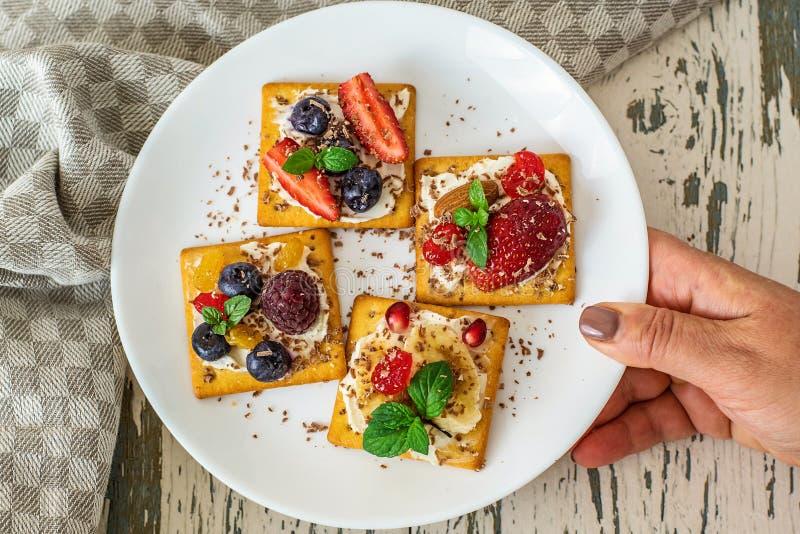 Placa branca em uma mão do ` s da mulher com biscoitos e vário fruto Vista superior fotografia de stock