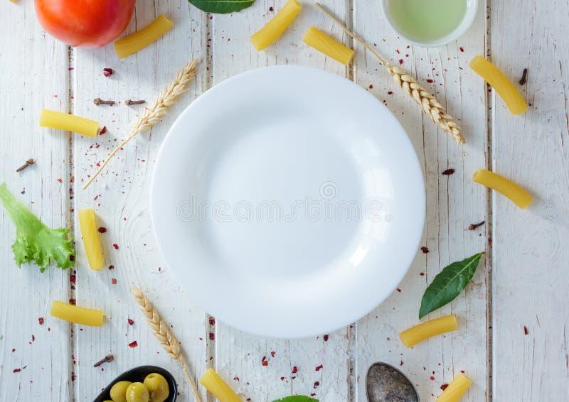 Placa cerâmica branca cercada pela massa italiana do tortiglioni, pelas folhas de louro e pelos outros ingredientes fotografia de stock royalty free