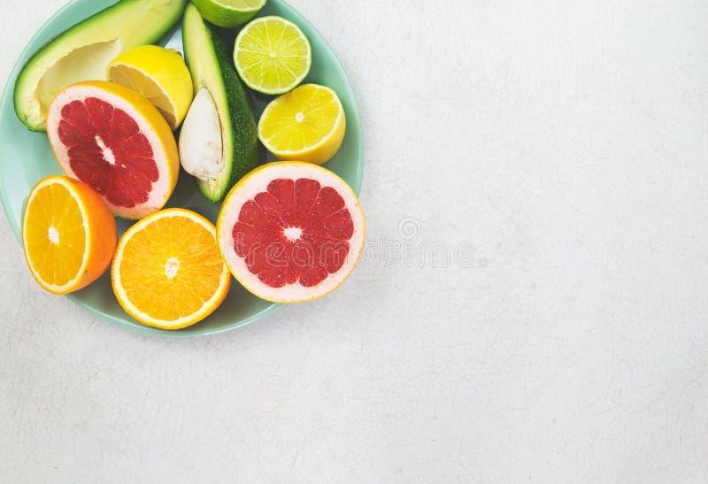 Placa ciánica con la naranja, el pomelo, el limón, la cal y el aguacate cortados en la tabla blanca vieja foto de archivo libre de regalías