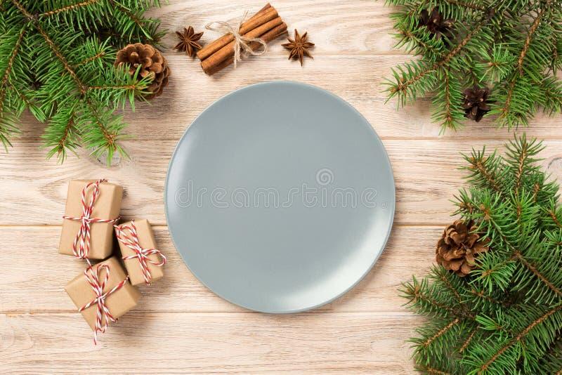 Placa cinzenta vazia do resíduo metálico no fundo de madeira com decoração do Natal, prato redondo Conceito do ano novo imagem de stock royalty free