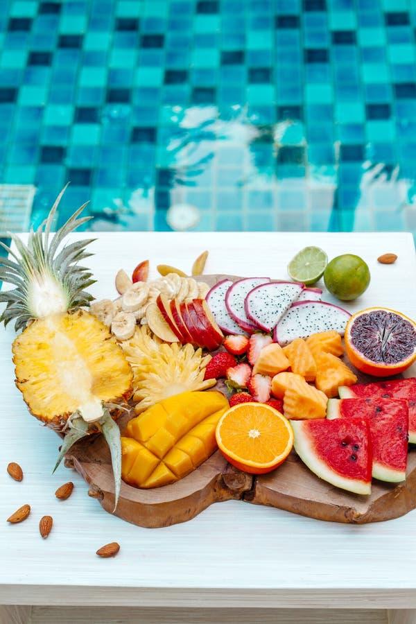 Placa colorida de la fruta tropical por la piscina fotografía de archivo