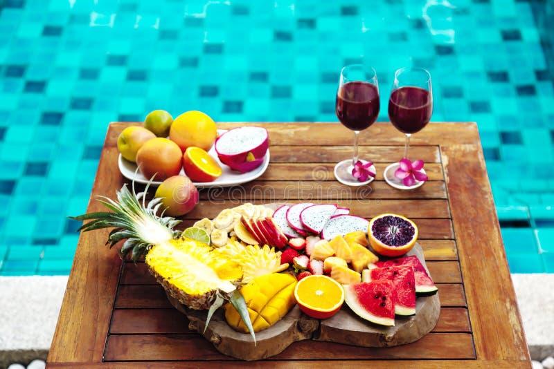 Placa colorida de la fruta tropical por la piscina imagen de archivo