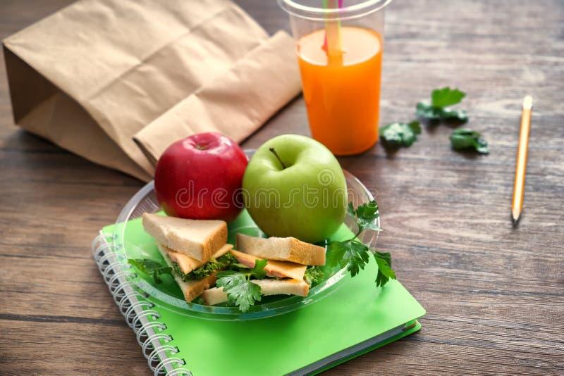 Placa com alimento apetitoso para o aluno e o copo plástico do suco na tabela de madeira imagens de stock