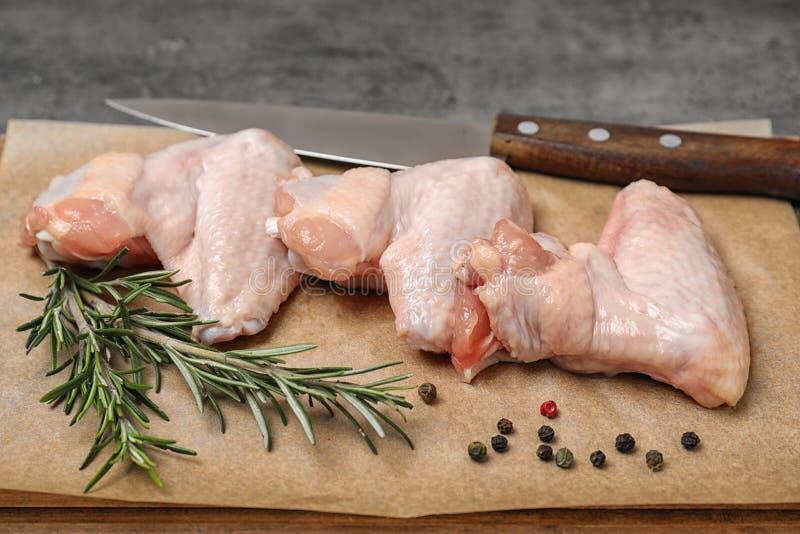 Placa com as asas e as especiarias cruas de galinha na tabela, close up fotos de stock