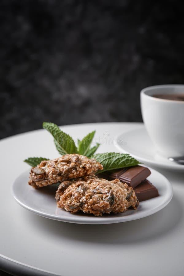 Placa com as cookies e chocolate deliciosos de farinha de aveia na tabela branca contra o fundo escuro fotografia de stock royalty free