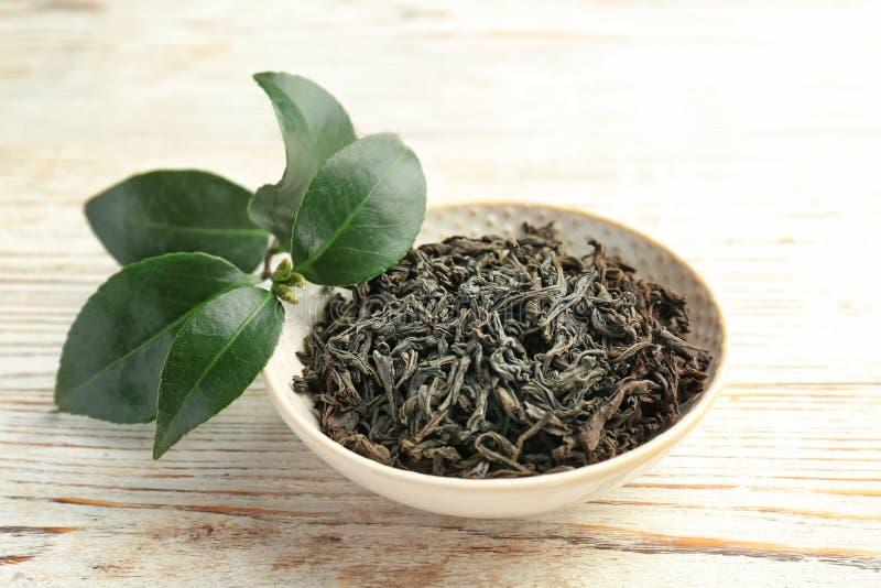Placa com chá seco e folhas verdes frescas na tabela fotos de stock