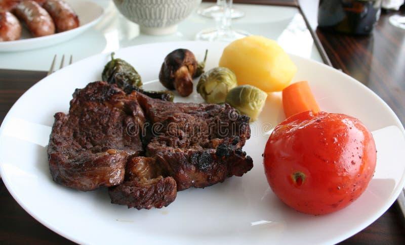 Placa com entrecote, batata, cenoura, couve-de-bruxelas, paprika e cogumelos - salsichas no fundo foto de stock