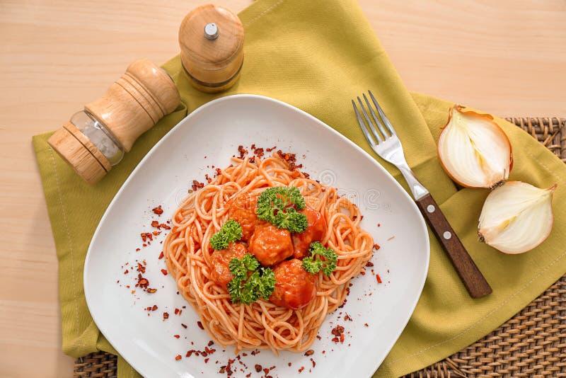 Placa com espaguetes e almôndegas na tabela Receitas deliciosas da massa foto de stock royalty free