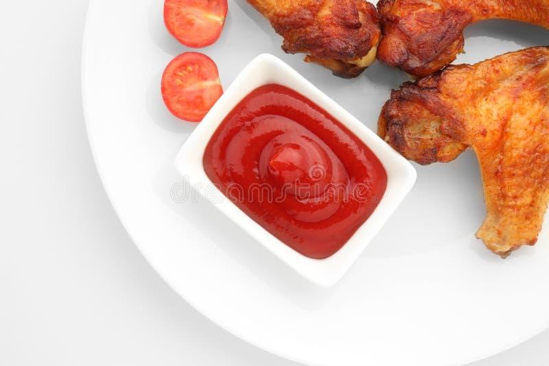 Placa com galinha roasted e molho de assado no fundo branco fotos de stock