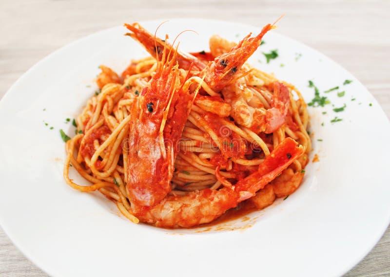 Placa com molho dos camarões, dos espaguetes e de tomate em uma taberna grega fotografia de stock