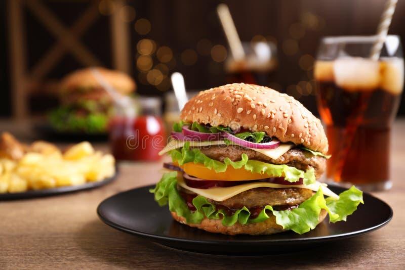 Placa com o Hamburger delicioso na tabela de madeira imagem de stock