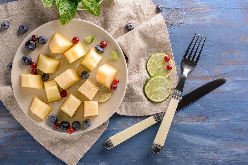 Placa com o melão cortado delicioso na tabela de madeira fotografia de stock