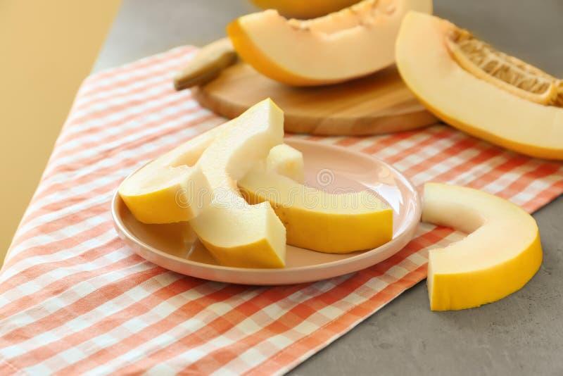 Placa com o melão cortado maduro na tabela imagem de stock royalty free