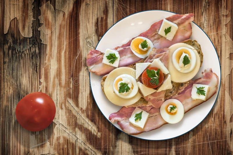 Placa com o presunto do ovo do queijo do bacon e o sanduíche do tomate em Woode velho fotografia de stock