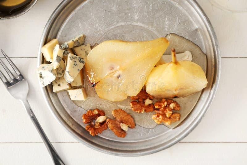 Placa com o queijo e a pera doce cozidos no vinho na tabela de madeira branca imagem de stock