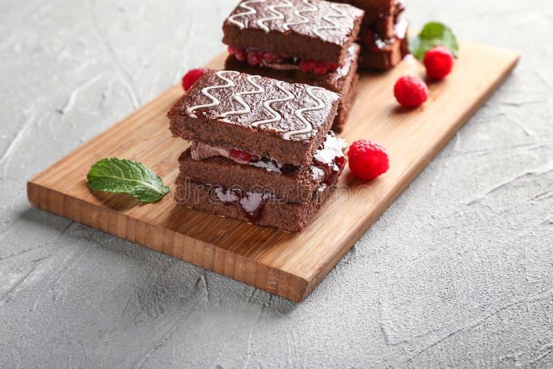 Placa com os bolos de chocolate saborosos e o doce de framboesa na tabela clara imagem de stock