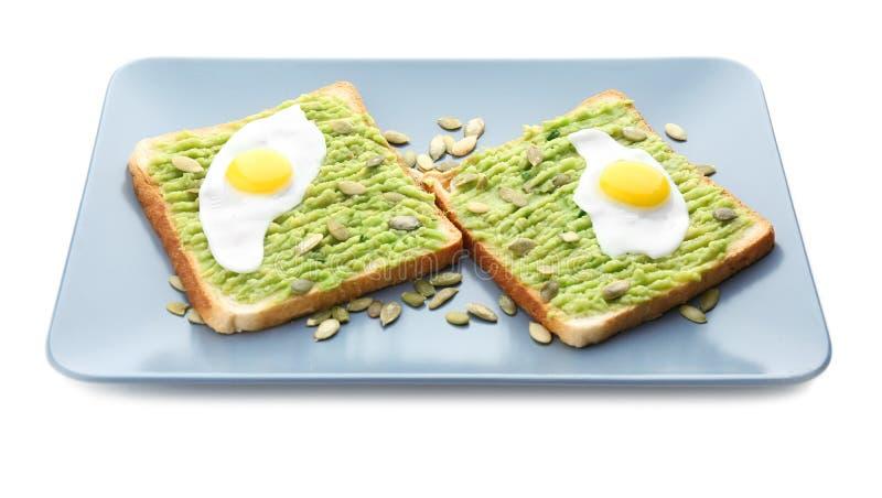 Placa com os brindes, a pasta do abacate e os ovos fritos, isolados fotografia de stock royalty free