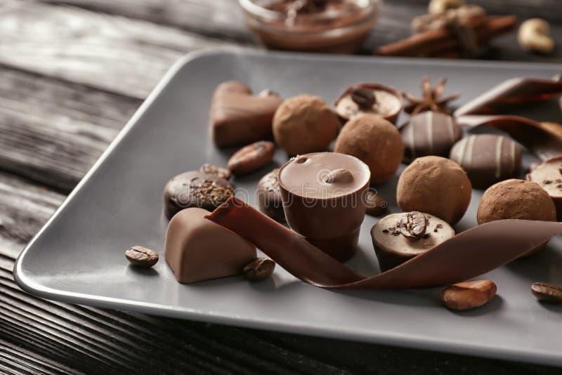 Placa com os doces de chocolate saborosos na tabela de madeira imagens de stock royalty free