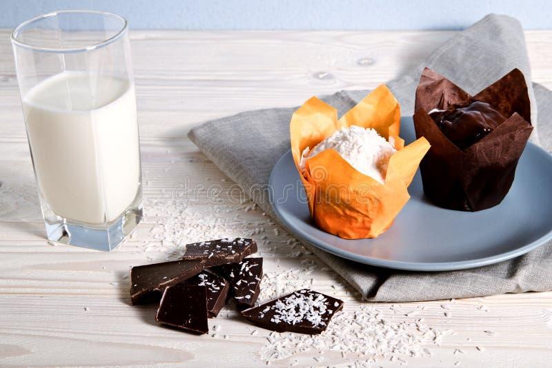 Placa com os dois queques recentemente cozidos Em seguida na tabela está um vidro do leite e das partes de chocolate preto, polvi fotografia de stock