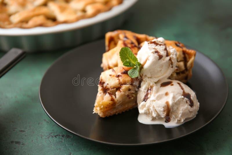Placa com parte de torta de maçã saboroso e de gelado na tabela foto de stock