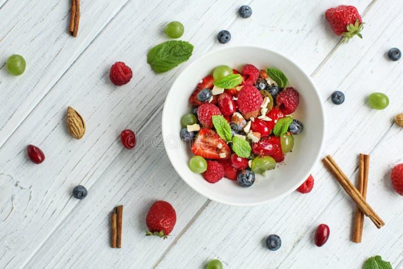 Placa com salada de fruto deliciosa na tabela de madeira branca foto de stock royalty free
