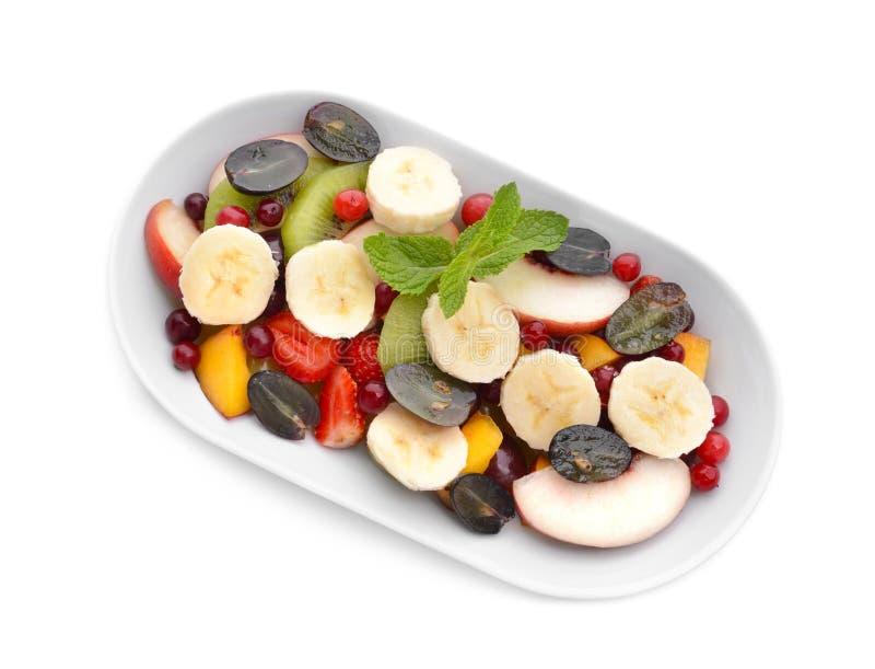 Placa com salada de fruto deliciosa no fundo branco imagem de stock