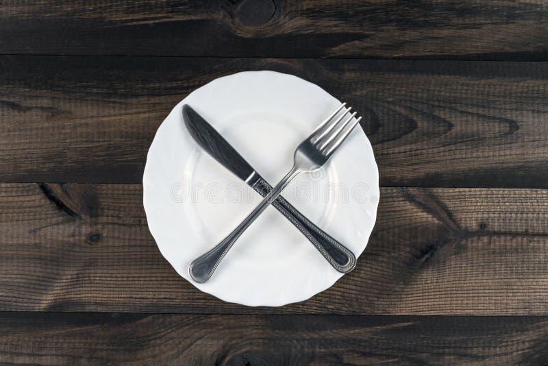 Placa con el cuchillo cruzado de la bifurcación y de mantequilla fotografía de archivo