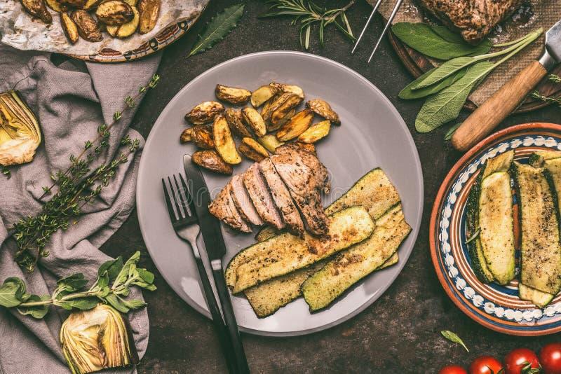 Placa con el filete asado a la parrilla del cerdo, carne asada y verduras frescas y patatas, placas y cubiertos cocidos en la tab fotografía de archivo