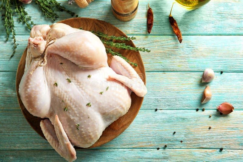 Placa con el pollo entero y el tomillo frescos foto de archivo