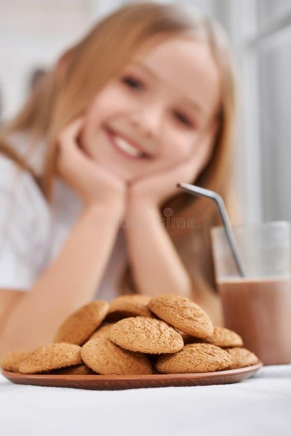 Placa con el vidrio de las galletas y del chocolate caliente en fondo de las niñas foto de archivo libre de regalías