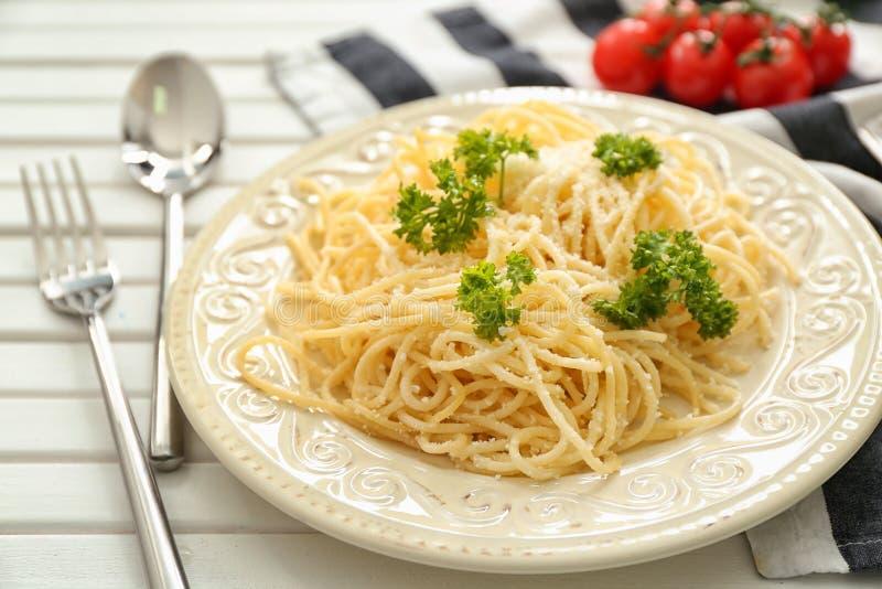 Placa con espaguetis y queso en la tabla Recetas deliciosas de las pastas imagen de archivo