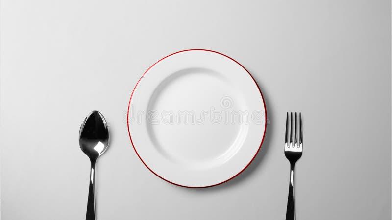 Placa con la cuchara y bifurcación en la fotografía común _isolated tabla blanca del fondo imagenes de archivo