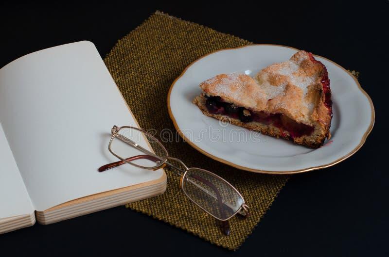 Placa con la empanada de la fruta, el cuaderno limpio sin notas y los vidrios en un fondo oscuro fotos de archivo