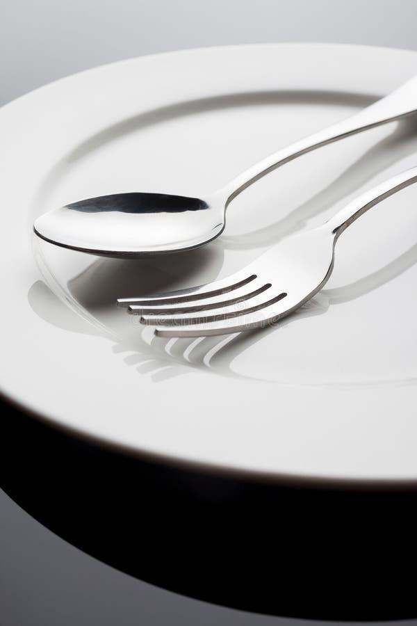 Placa con la fork y la cuchara foto de archivo